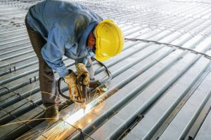 Steel deck framing by worker with a hard hat on and power tool